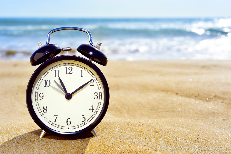 closeup of an alarm clock on the sand of a beach adjusting forwa