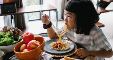 child eating pasta at table apples